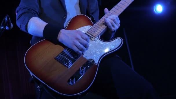 Muž si hraje rocková píseň na elektrickou kytaru v nočním klubu. detail. Zpěvák hry dřevěné elektrická kytara na jevišti