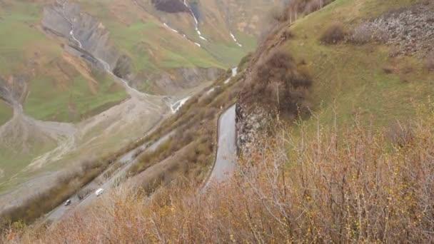 Horská krajina. Silnice, procházející v horách. Automobily jsou jízdy po silnici v horách. Silniční serpentine v pohoří Kavkaz. Dopravní automobily pohled shora doprava