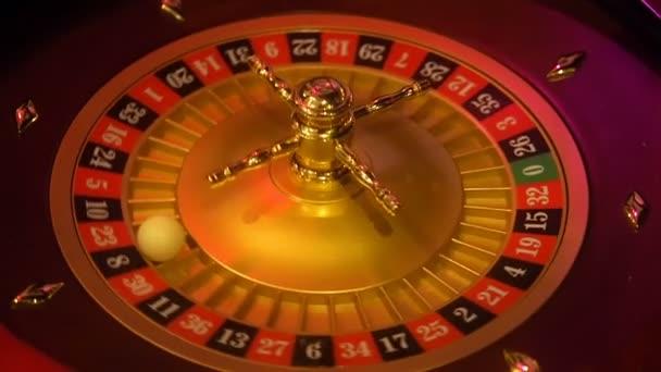 Kasino ruleta v pohybu s točícím se kolem a míč. Vítězné číslo 8 a barva Černá určuje ruleta kolo. Rozložení tabulky rulety za slabého světla.