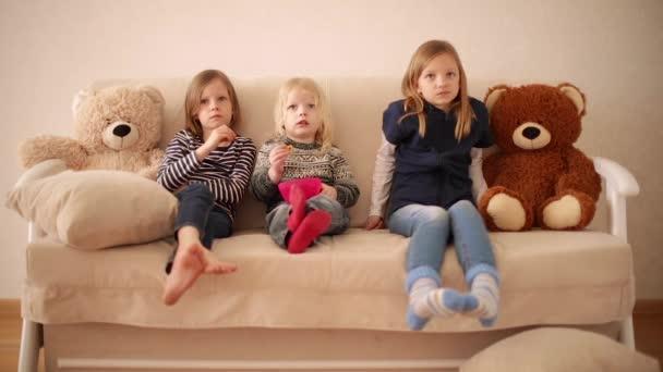 Vtipný malý chlapec (3 roky) sleduje kreslené seriály se staršími sestrami (8 a 9 let). Bratři a sestry sedí na gauči a jedí sušenky.