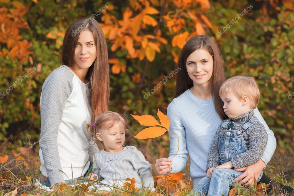 Alternative lesbian family with mothers, daughter and boy outdoo
