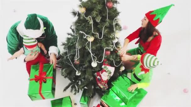Šťastná rodina, zdobení vánočního stromu, oblečený v skřítek kostýmy