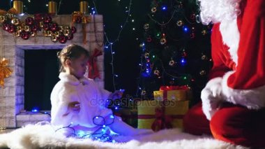 Santa and girl playing near fireplace, decorated Christmas tree
