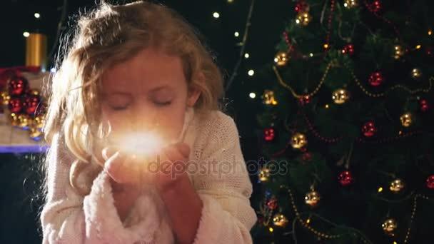 Aranyos lány tündér fúj mágikus csillogó karácsony éjjel.