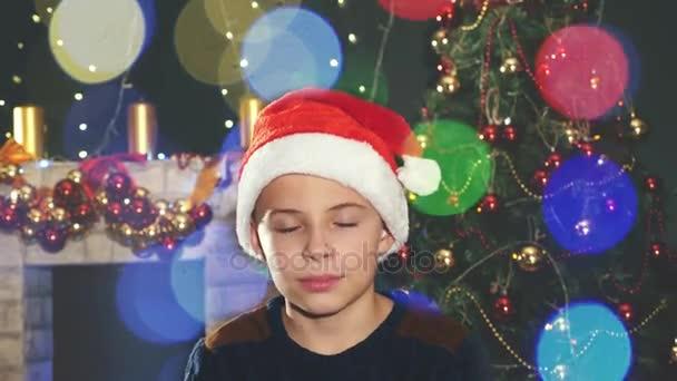 Šťastný chlapec v Santa hat blízko zdobené vánoční strom