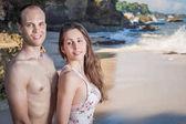 Šťastný pár na pláži, výhled na moře. Cestování na Bali.