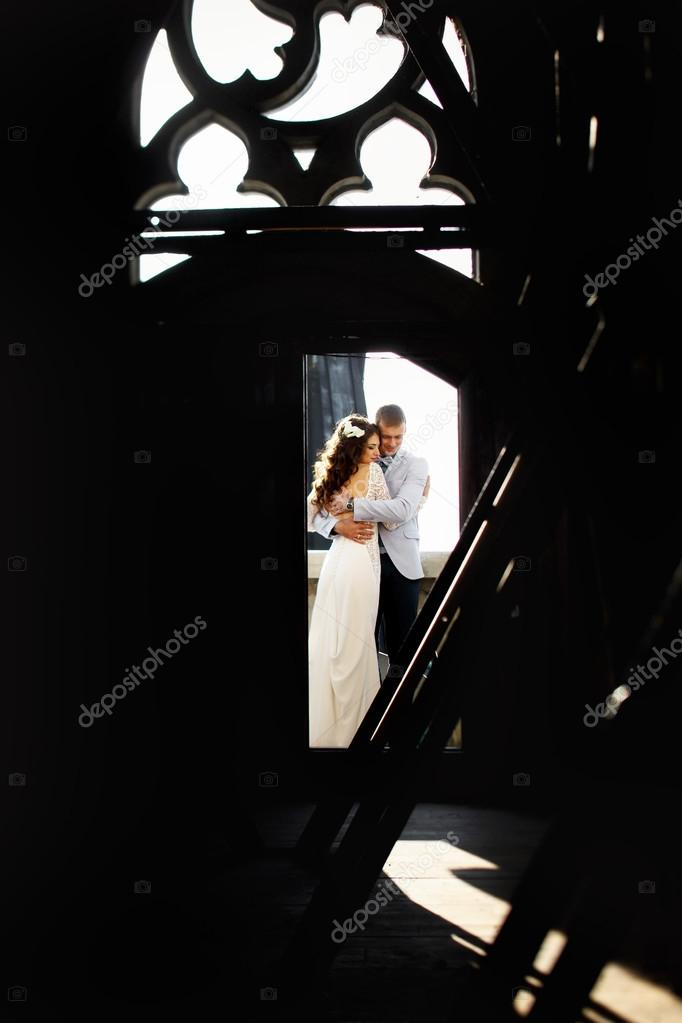 Bride and fiance hug in the door to rooftop of Gothic cathedral