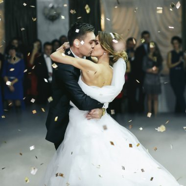 Just married kiss in the thick smoke and the rain of confetti