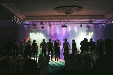 People dancing in the neon lights during the wedding party