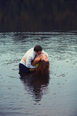 Man kisses woman's neck standing in water