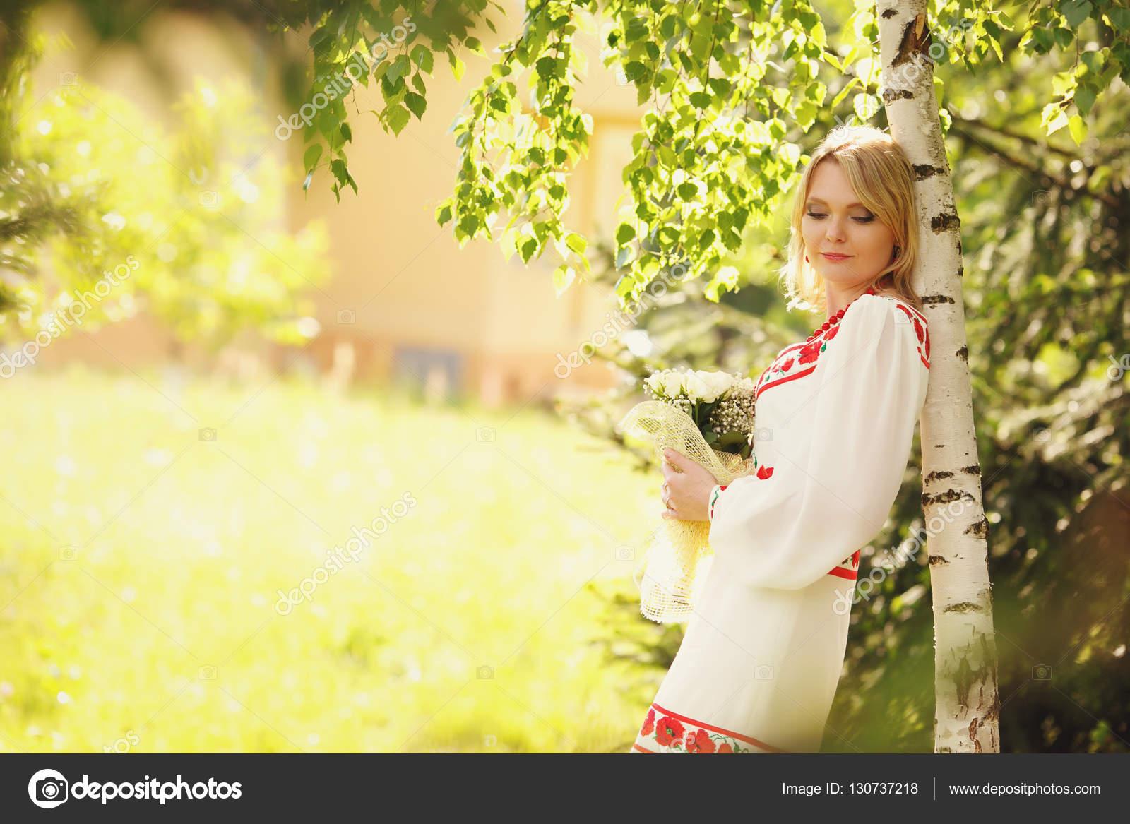 Наречена одягнений у біле плаття з маками нахиляється до за береза у парку  — Фото від ivash b81c6c2a8e44a