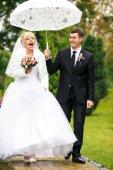 Fényképek Séta alatt egy esernyő, birtokában egy vőlegény menyasszony nevet
