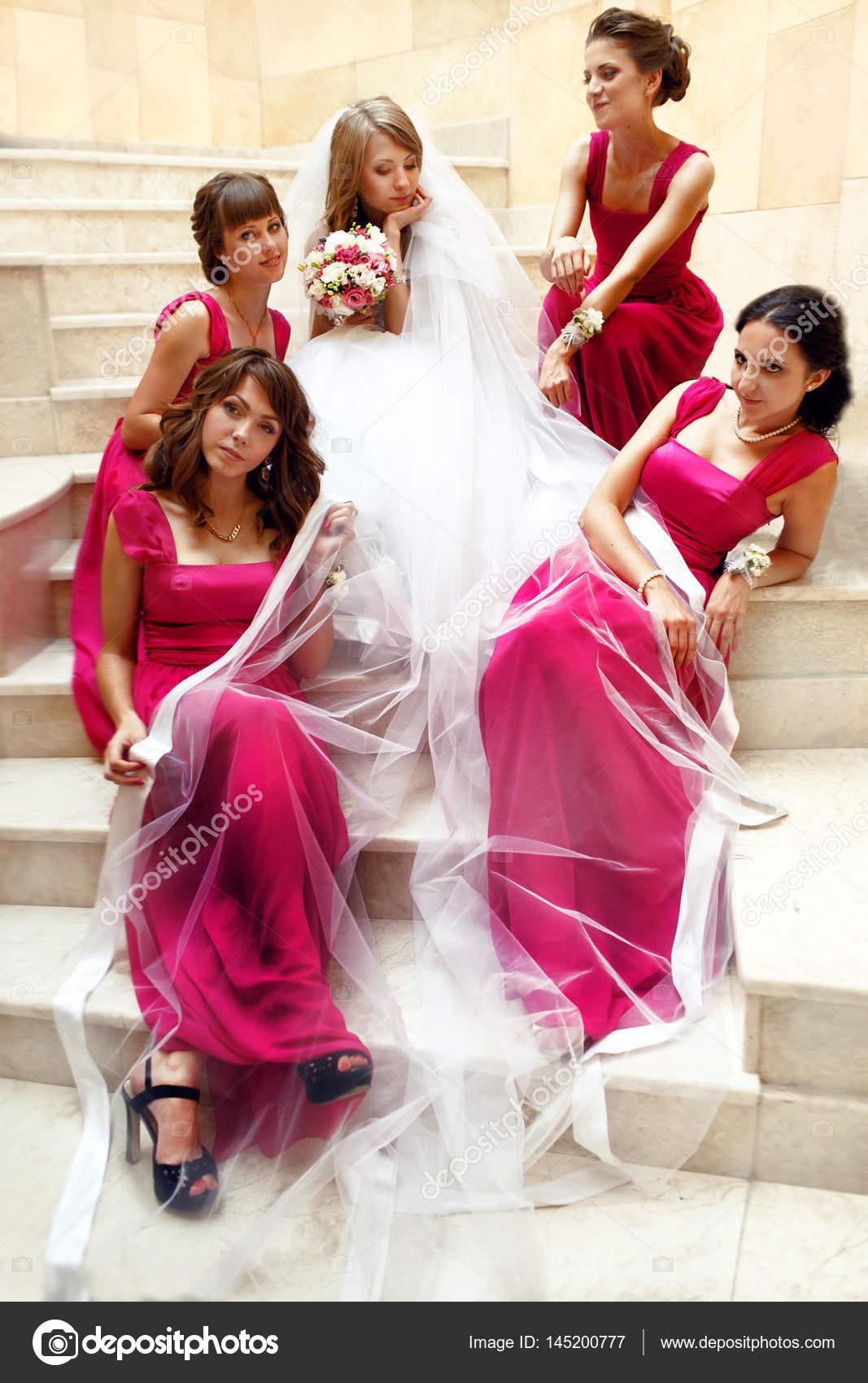 Las damas de honor en vestidos rosa rodeado a una novia sentado bajo ...