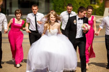 Wind blows bride's hair while she and groom walk in the park sur