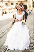 Fényképek Menyasszony nevet, míg a vőlegény megcsókolja a nyakát valahol a régi
