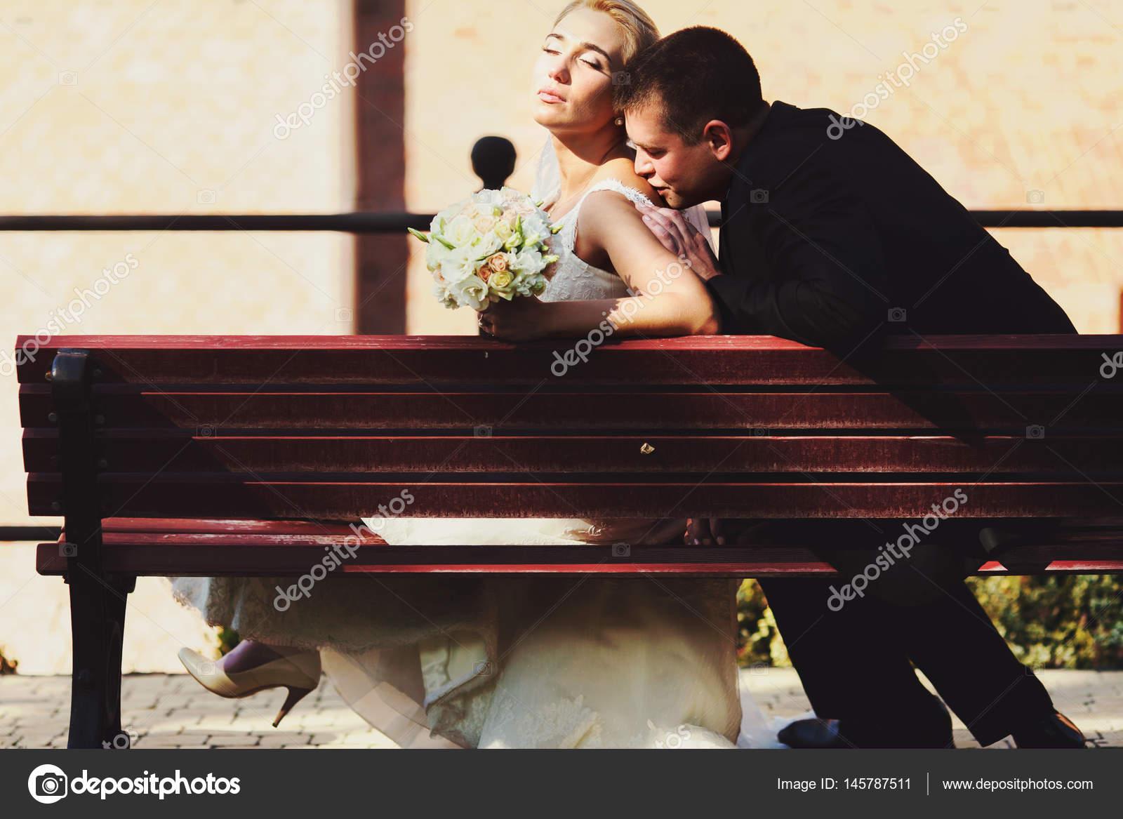 Noivo beija o ombro da noiva enquanto descansam nos raios solares em —  Fotografia de Stock 947ce9fde23