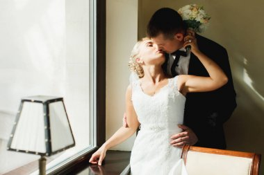 Bride kisses a groom while he hugs her from behind standing in t