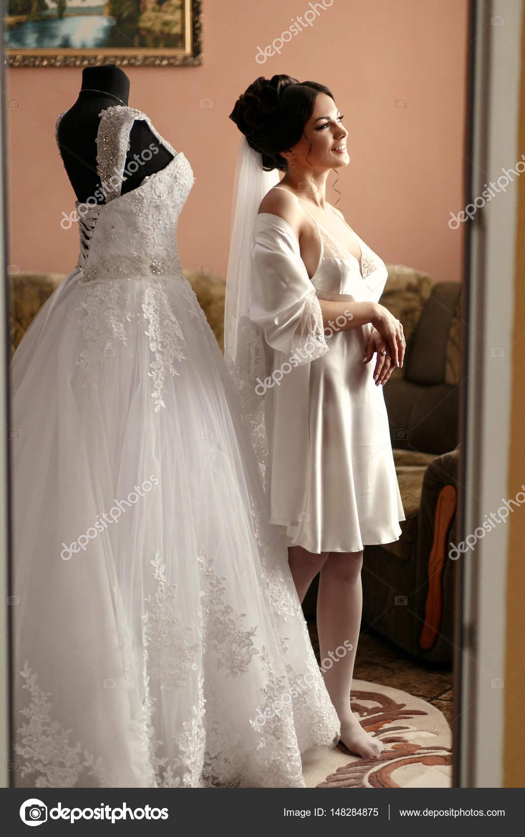 Die Braut steht in der Nähe von Brautkleid in das Zimmer — Stockfoto ...