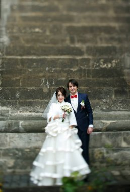 Pretty wedding couple pose on the pass behind an old gray wall
