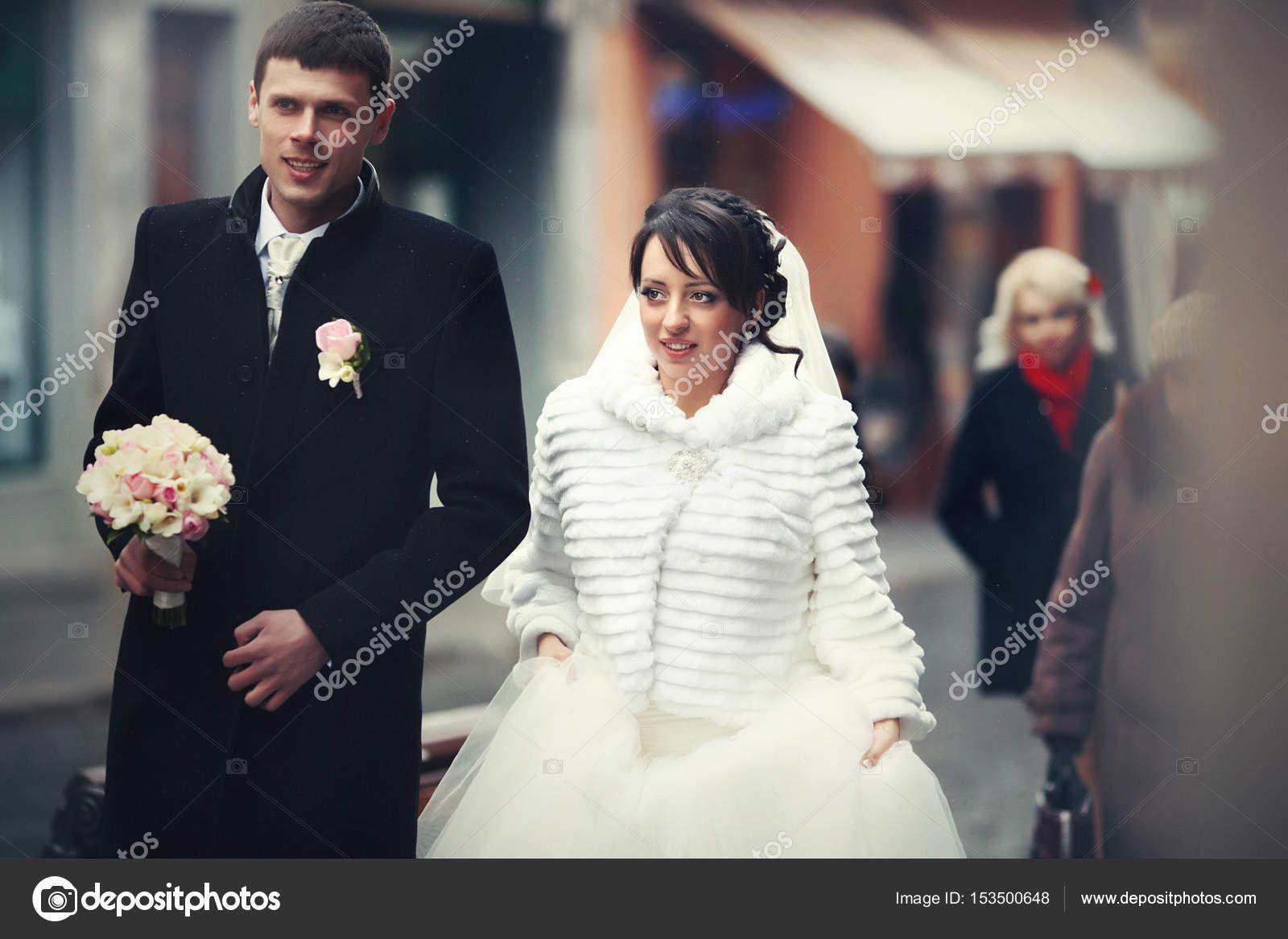 d5f835fb3a51 Sposa e sposo in cappotti di inverno a piedi lungo l antica via — Foto