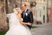 Fényképek Szőke menyasszony nevet háta mögött komoly vőlegény