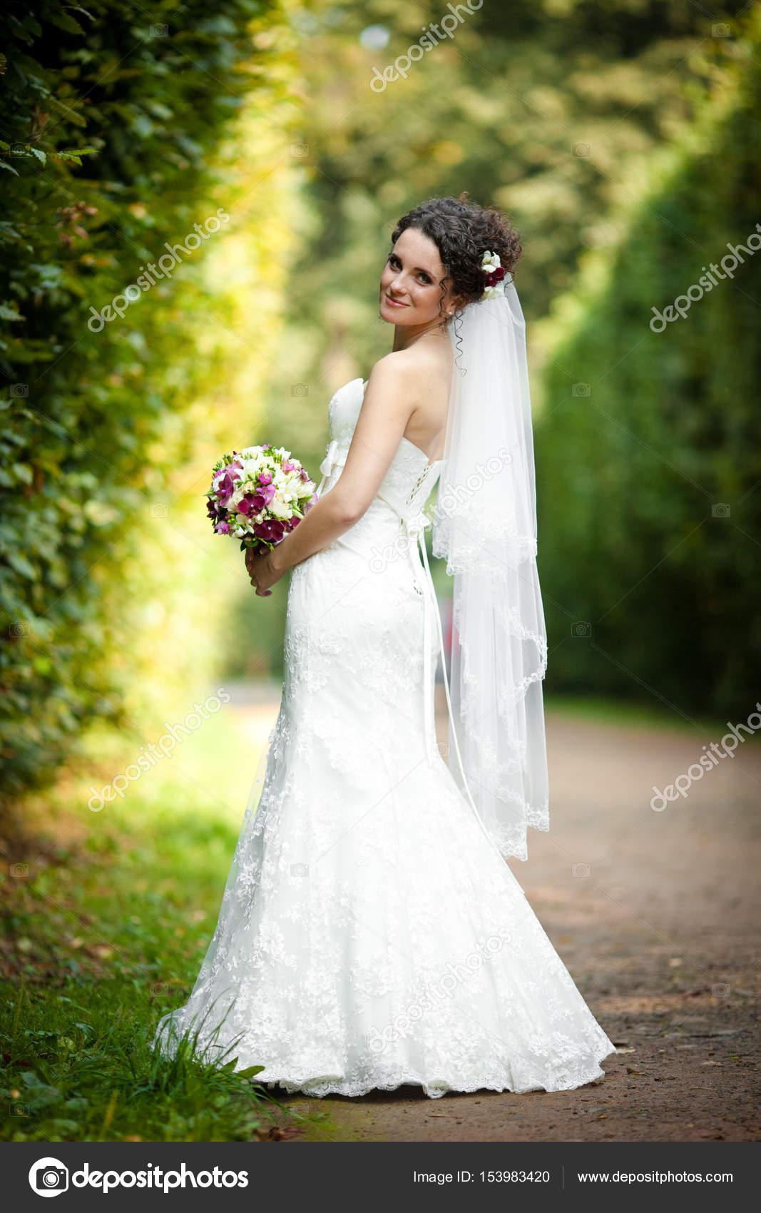 Elegante Braut im langen weißen Kleid Posen in den grünen park ...