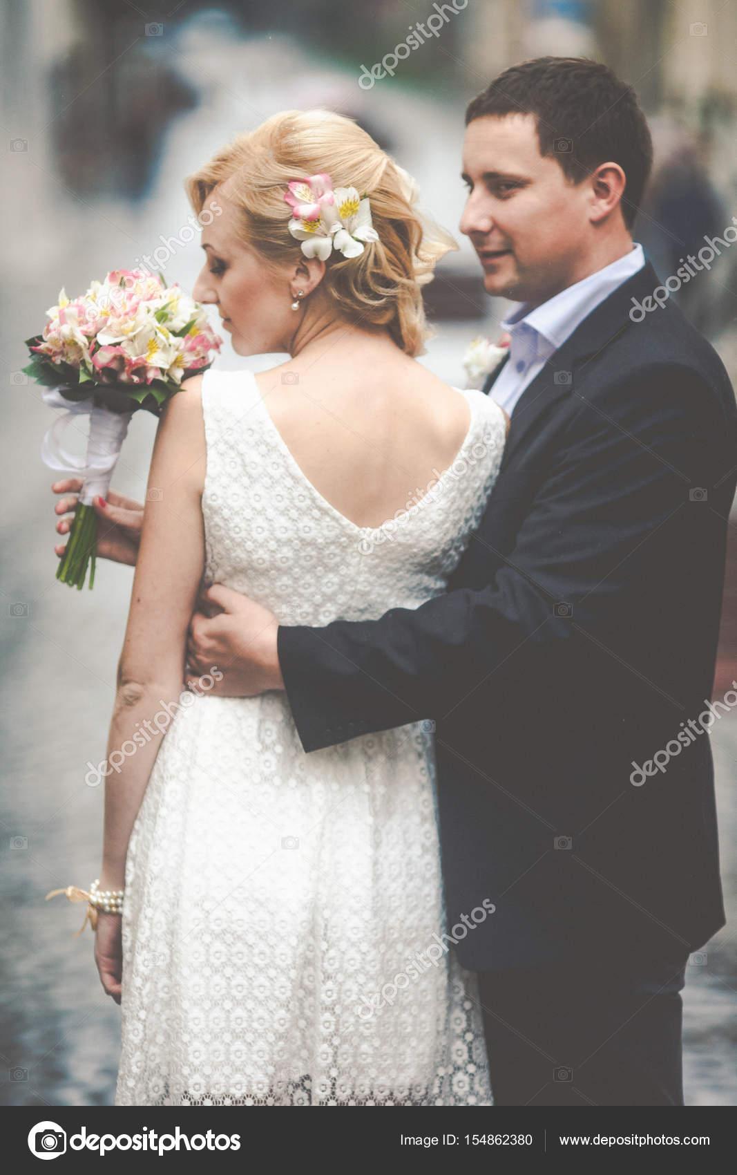 Braut steht Sommerkleid kurz hinter einem Bräutigam Hochzeit b ...