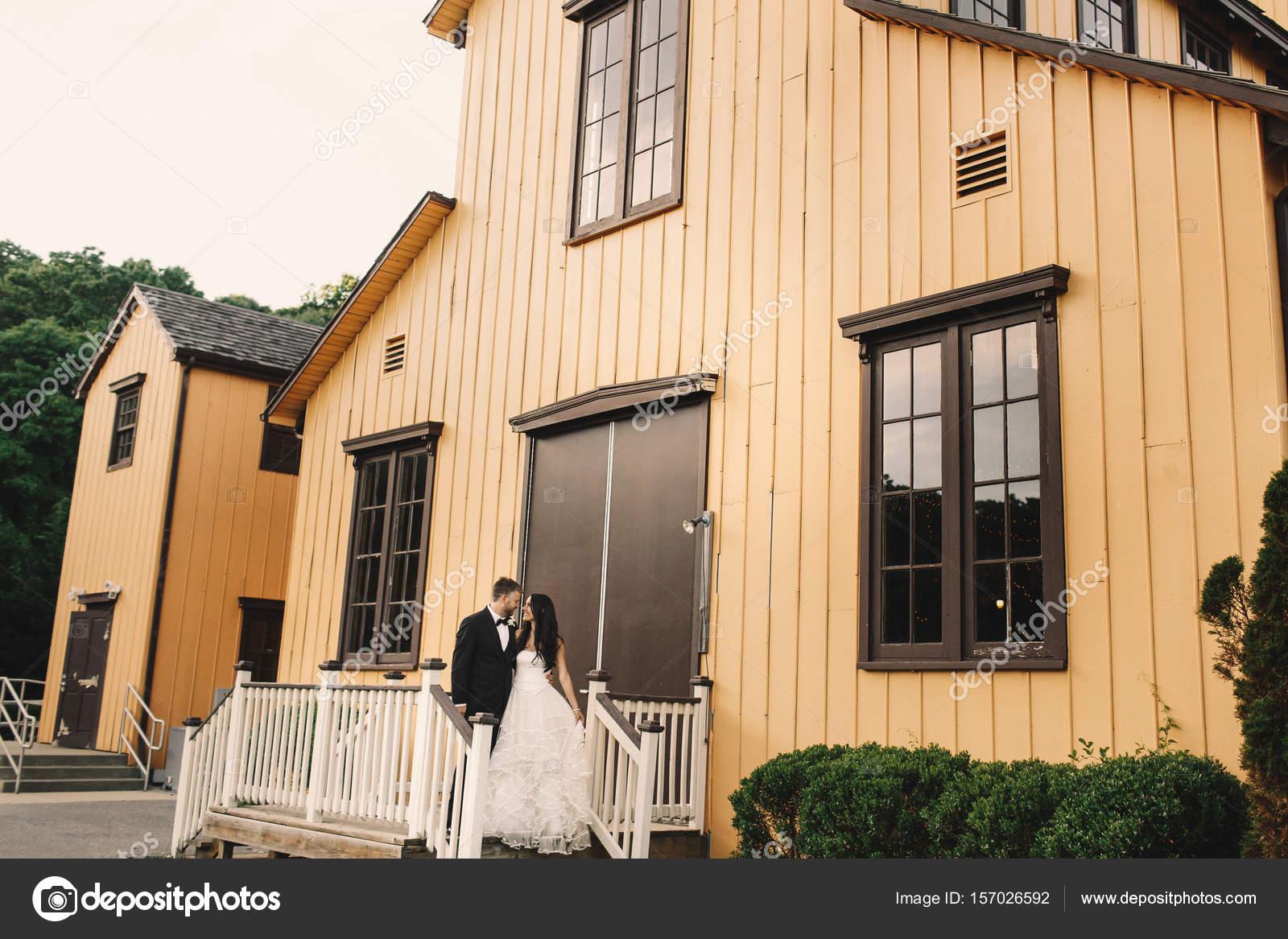 Le Porche De La Maison magnifiques jeunes mariés posent sur le porche de la maison en bois