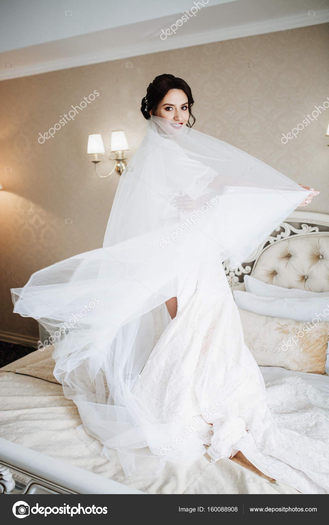 Braut steht mit Brautkleid auf dem Bett — Stockfoto © ivash #160088908