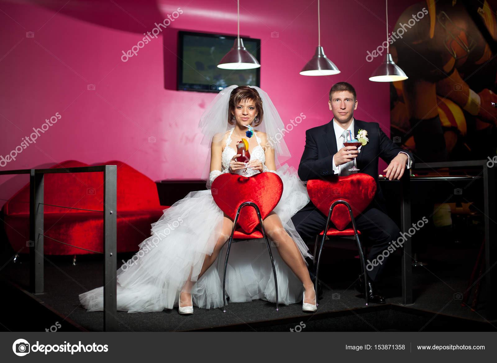 la pareja en el día de la boda sentado en las sillas rojas con el ...