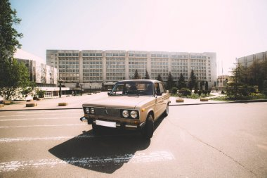 A retro car made in the USSR stands on the background of Kiev Polytechnic Institute. Kiev, Ukraine.