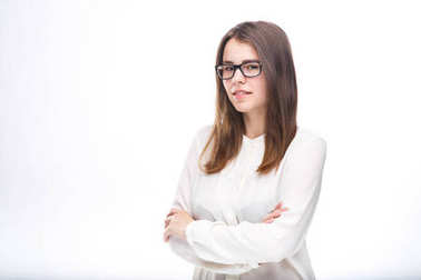 beautiful young girl in glasses with black frame, with brown hair over shoulders and white shirt on white isolated background.
