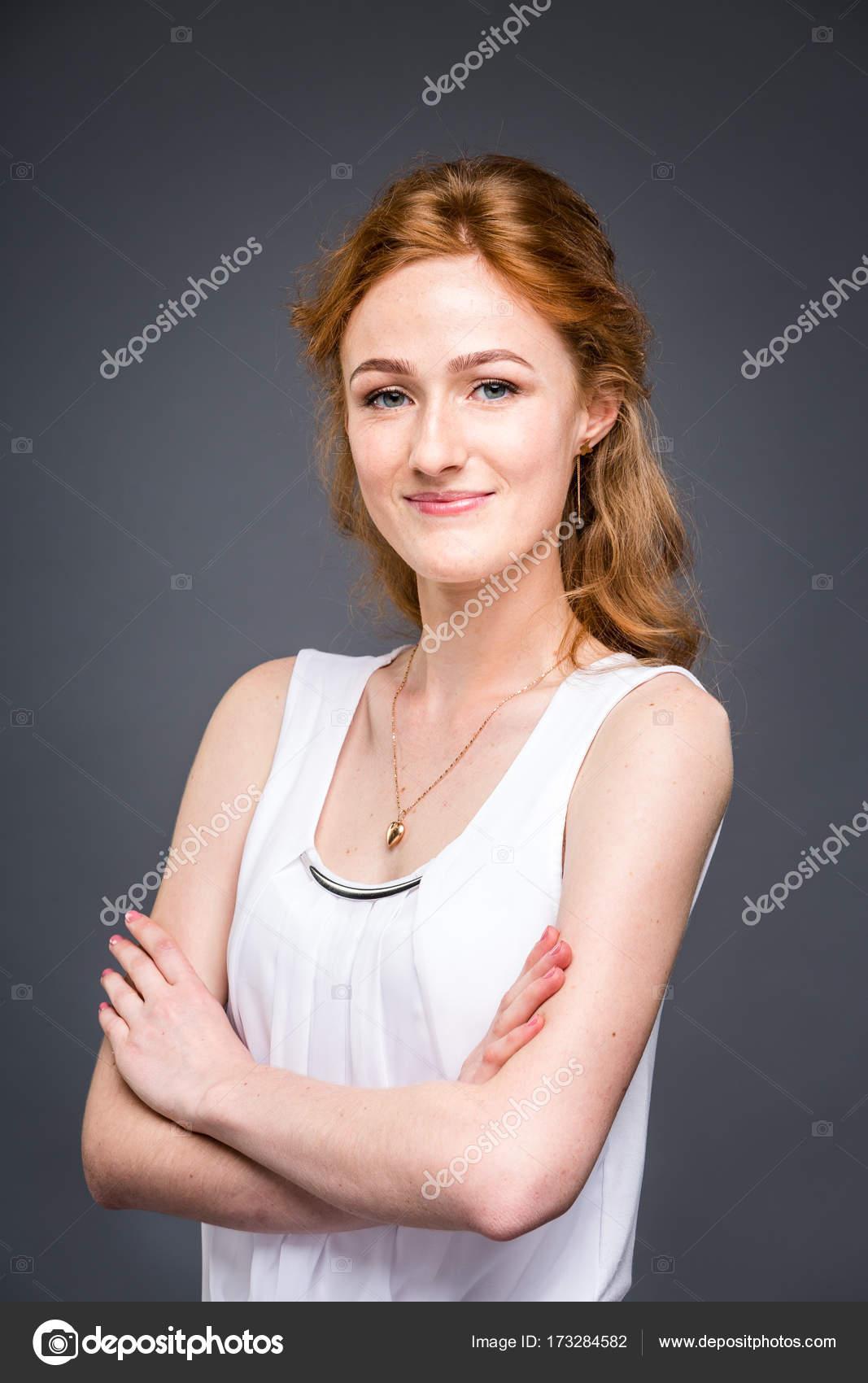 c037f015248c Ritratto di un giovane redhaired bella ragazza in studio su un grigio  isolato sfondo. Una donna è in piedi con le braccia conserte e sorridente  in una ...