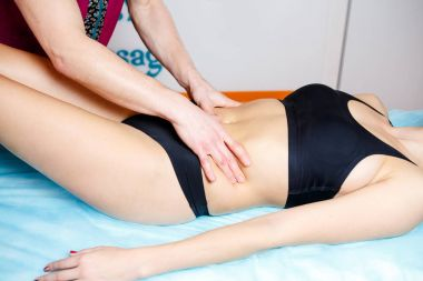 the hands of a masseur make a relaxing massage to a woman on the abdominal abdomen for toning the muscles. Close-up