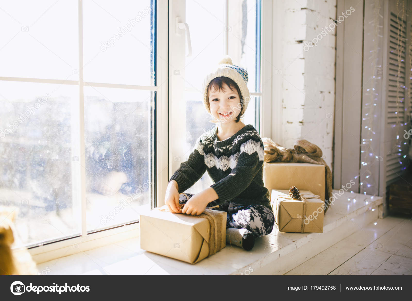 niño está sentado junto a la ventana en un día soleado de la Navidad ...