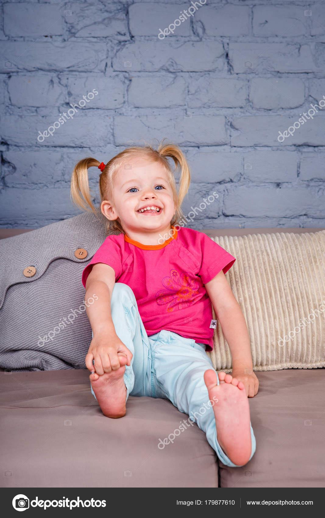 la niña divertida permite en el sofá en casa con las manos detrás de ...