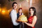 Téma rodinná dovolená Dětské narozeniny a sfoukl svíčky na velký dort. mladá rodina ze tří lidí, postavení a držení 5 letou dceru ve dvoře šedé zdi a věnec žluté cibule