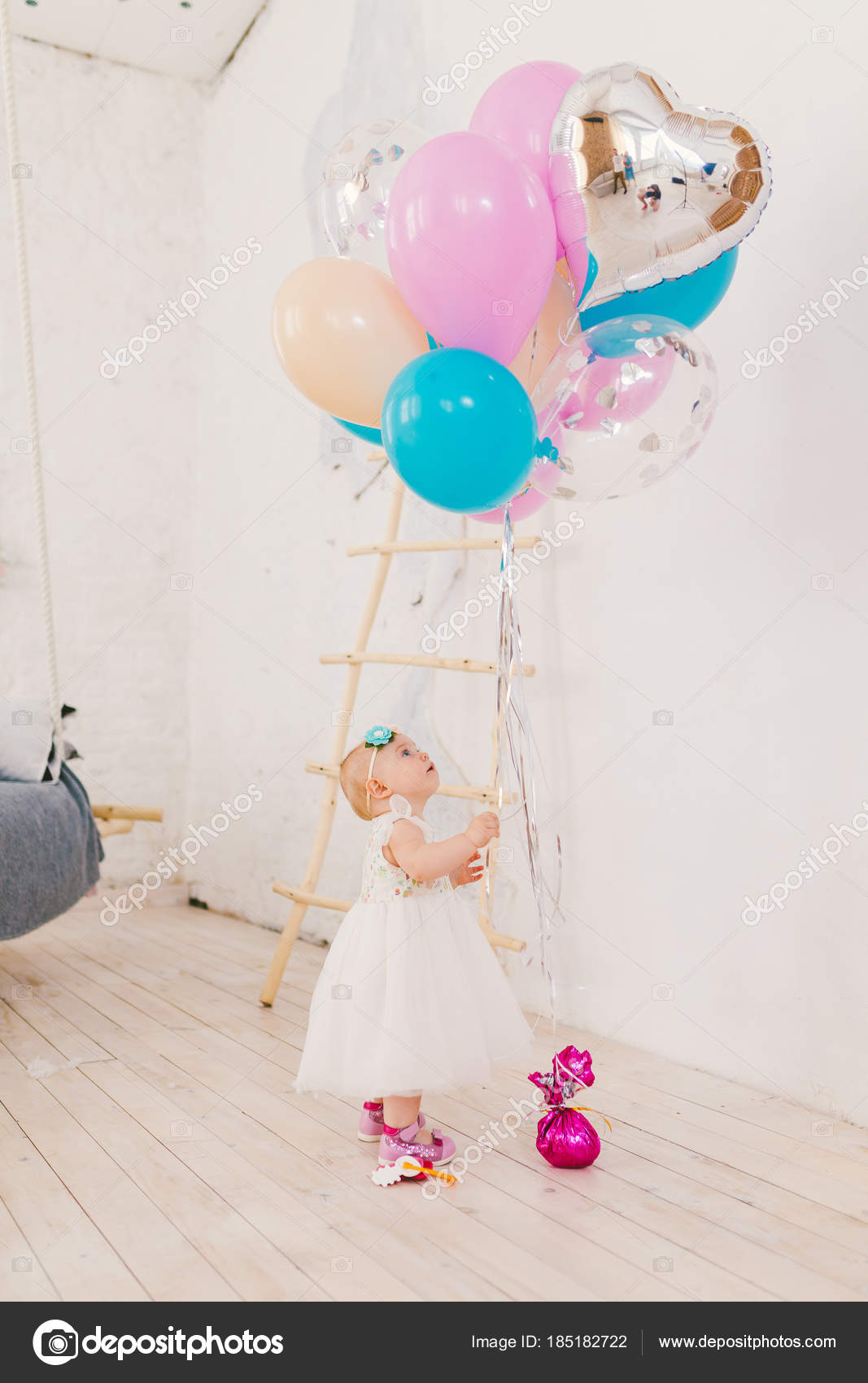 Ein Kleines Mädchen Im Weißen Kleid Aufwendigen Steht Im Wohnzimmer Im Haus  In Der Nähe Der Dekorative Treppe Und Erstreckt Sich Auf Haufen Von Bunten  ...