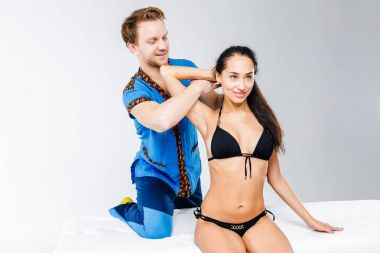 Theme massage and body care. young doctor masseur in working suit makes massage for stretching the muscles of the neck, shoulder and hands of a beautiful girl sitting on a table in a black swimsuit