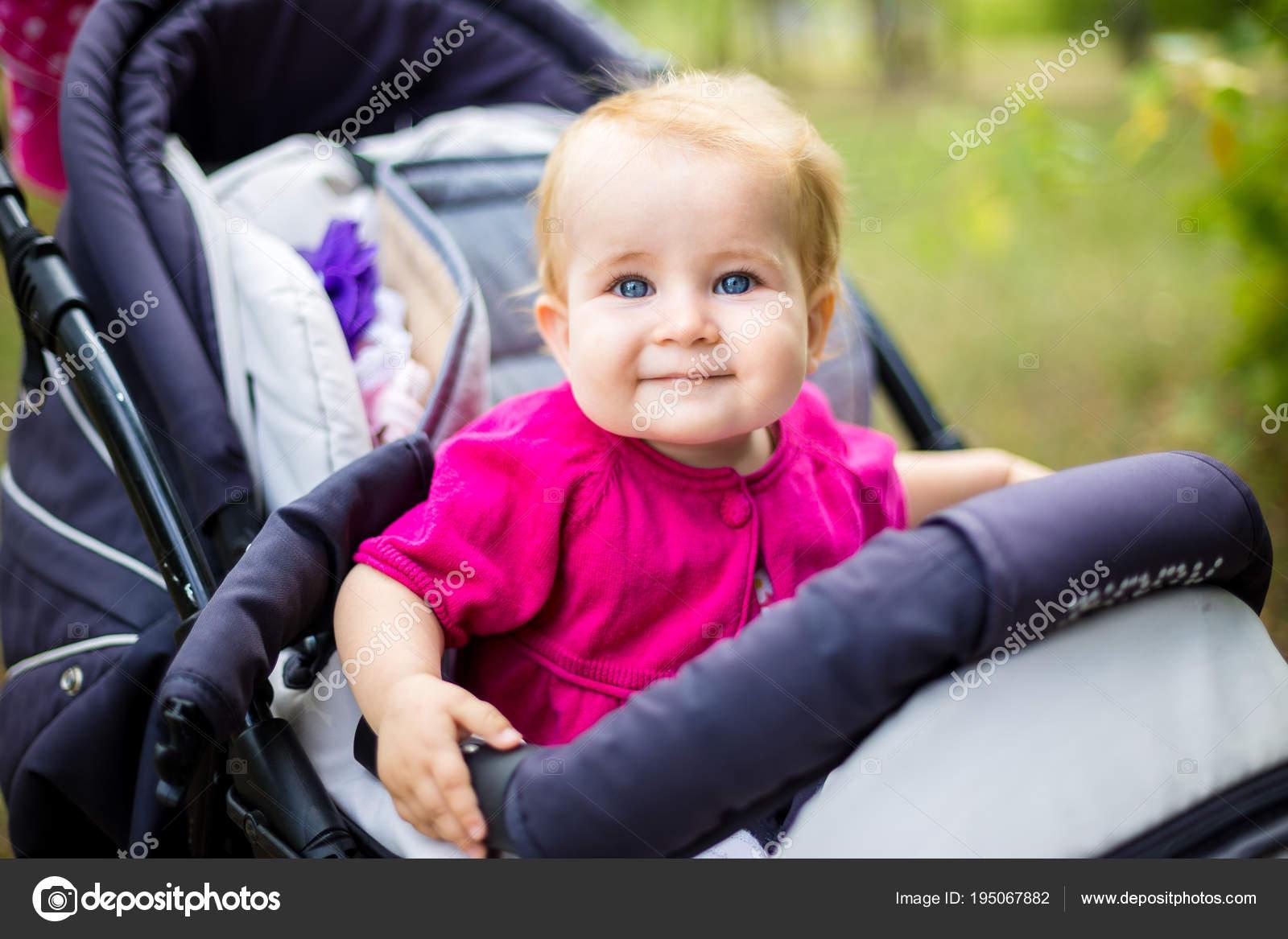 009c45e5f698 Portrait d un petit blond de fille drôle enfant aux yeux bleus, assis dans  une poussette de bébé durant l été pour les verts. Trinasport pour un enfant  et ...