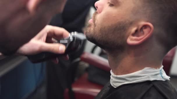 Holič holí klientům vousy na židli. Ostříhat vousy. Holič si holí vousy elektrickým holicím strojem. Pečovat o opravdového muže. Boční pohled na mladé vousatý muž dostat vousy sestřih na kadeřnictví