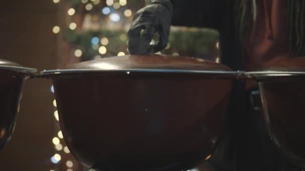 Große Pfannen mit heißem Glühwein zur Weihnachtszeit. Straßenladen mit traditionellem Glühwein. Glühweinpfanne aus nächster Nähe am Abend auf dem Weihnachtsmarkt. Street Food, Glühwein in Kübel auf Feuer gekocht