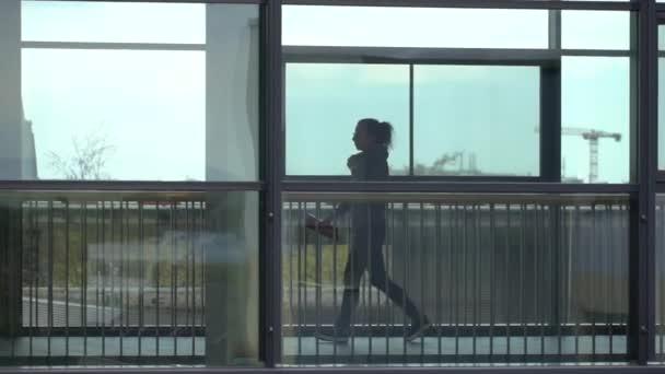 Silueta osoby kráčející uvnitř budovy. Exteriér moderní kancelářské budovy a muž v siluetě procházející kolem oken