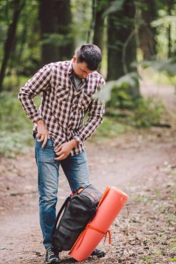 guy with backpack, traveller, hipster standing in woods, Hiking, Forest, Journey. Caucasian tourist man packs rucksack, takes things. Man having break during hike in wood. looking into travel bag