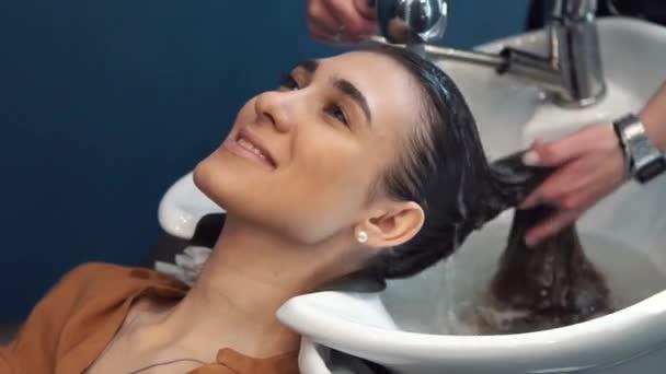 Krása, vlasná péče a lidé koncept-šťastná mladá žena se kadeřnicí v kadeřnictví