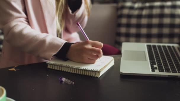Közelkép kaukázusi nő kezét a fa asztal belsejében kávézó jegyzetel jegyzetfüzetbe. Az alany szabadúszó blogger újságíró a munkahelyén. Felismerhetetlen személy. Technológia telefon és laptop csésze kávéval