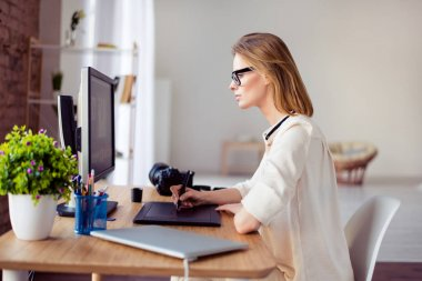 Side view  of female graphic designer working with interactive p