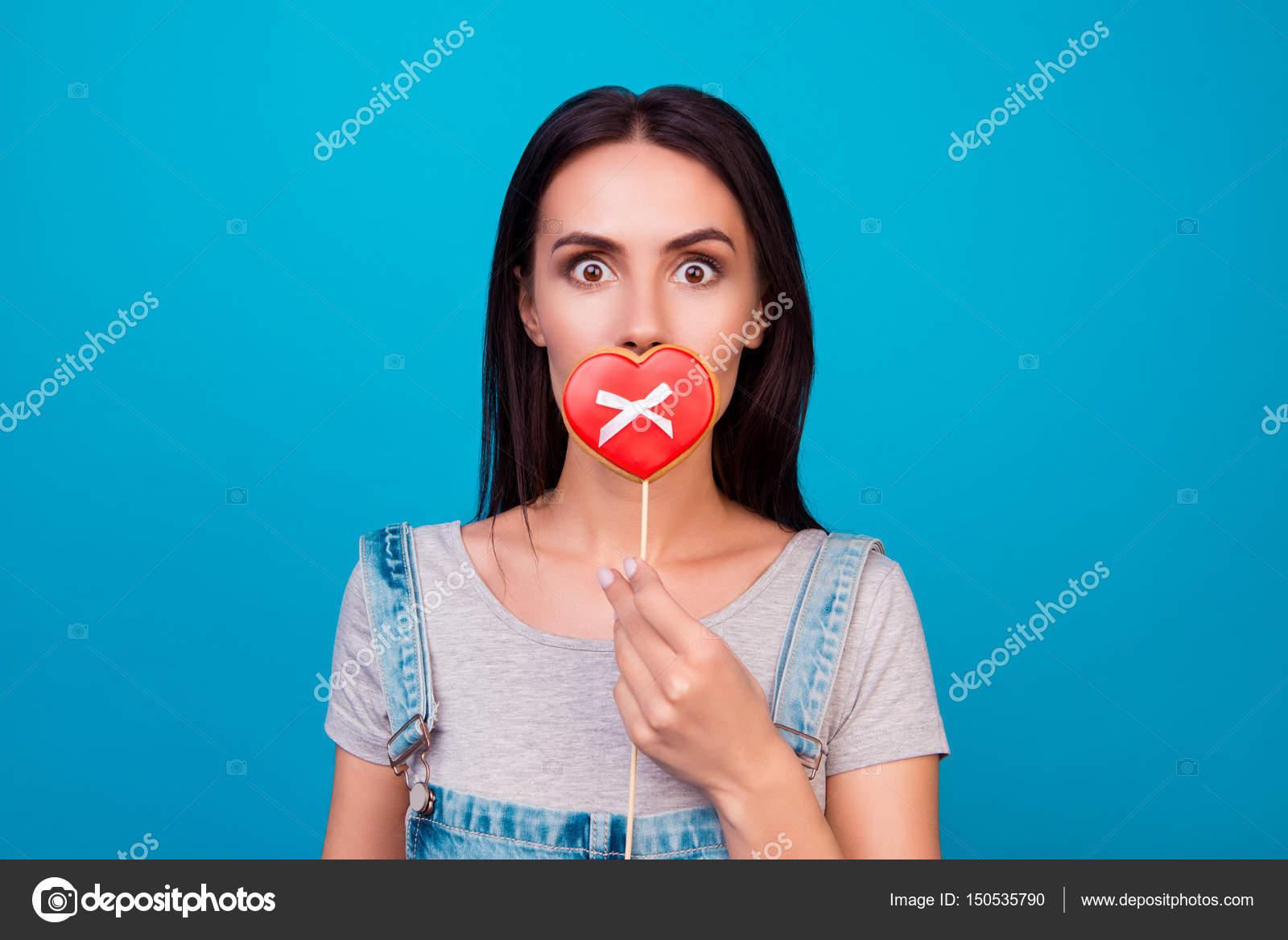 Junge fröhliche Frau auf blauem Hintergrund schließen den Mund mit c ...