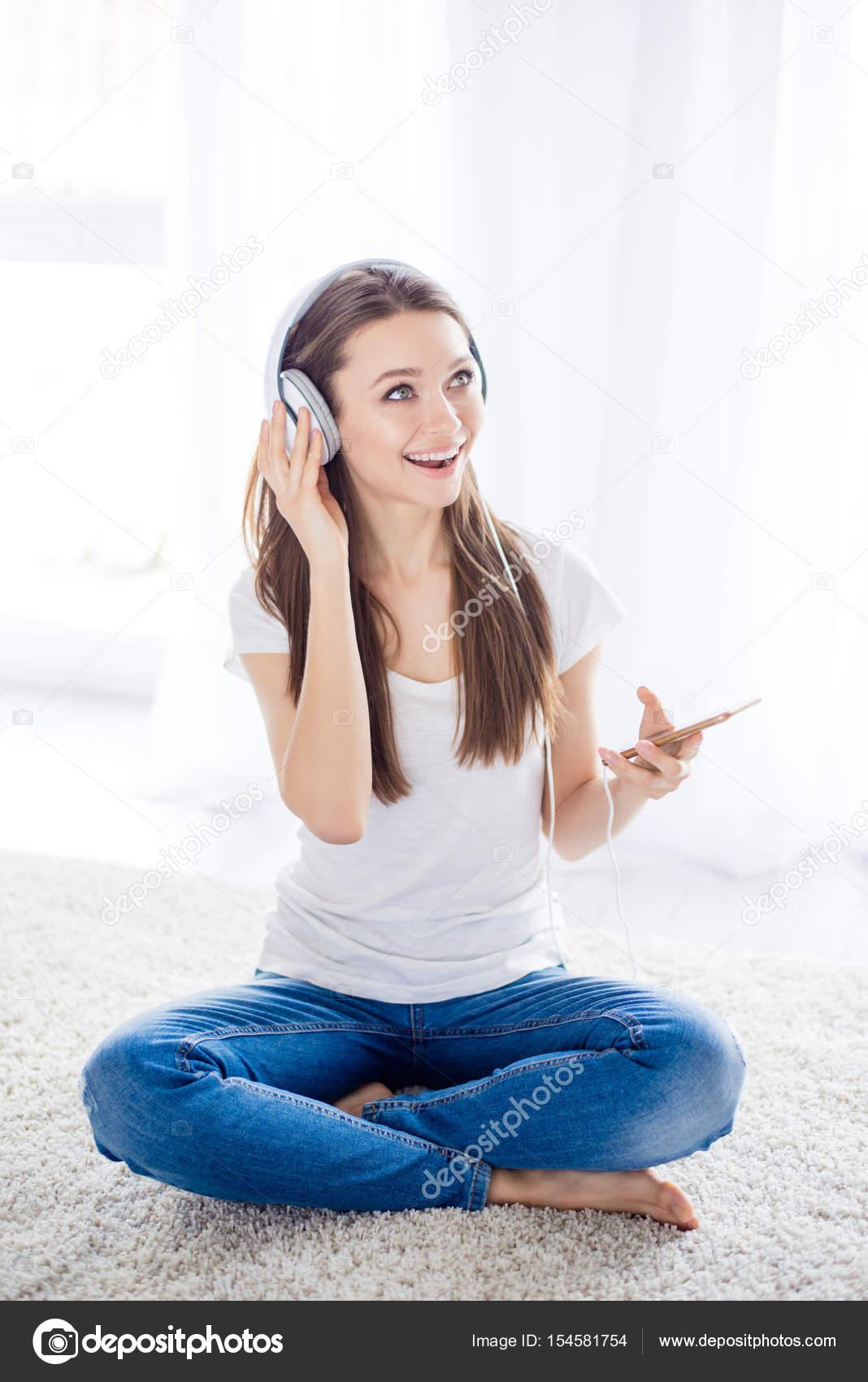 Energikus fiatal lány zenehallgatás fejhallgató ült a földön. Ő fordult a  neki a kedvenc rövid színdarab — Fotó szerzőtől deagreez1 c12b944dca