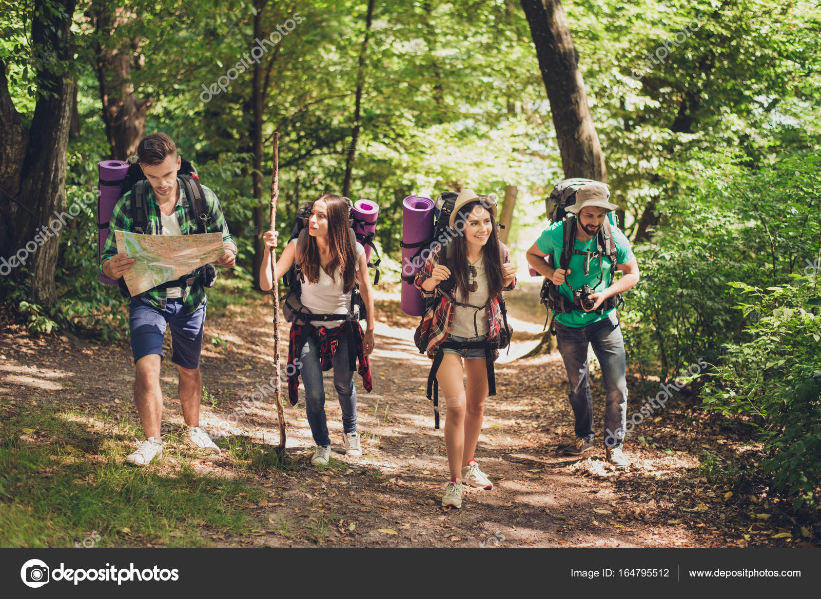 trekking camping and wild life concept four best friends are hiking in the spring woods people woods g11 camping